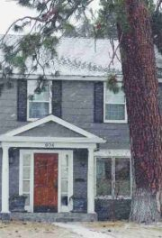 Grey house with red door and tree in front