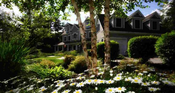 Large grey house with flowers and trees in yard