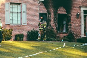 Firefighter leaving a smoke damaged house